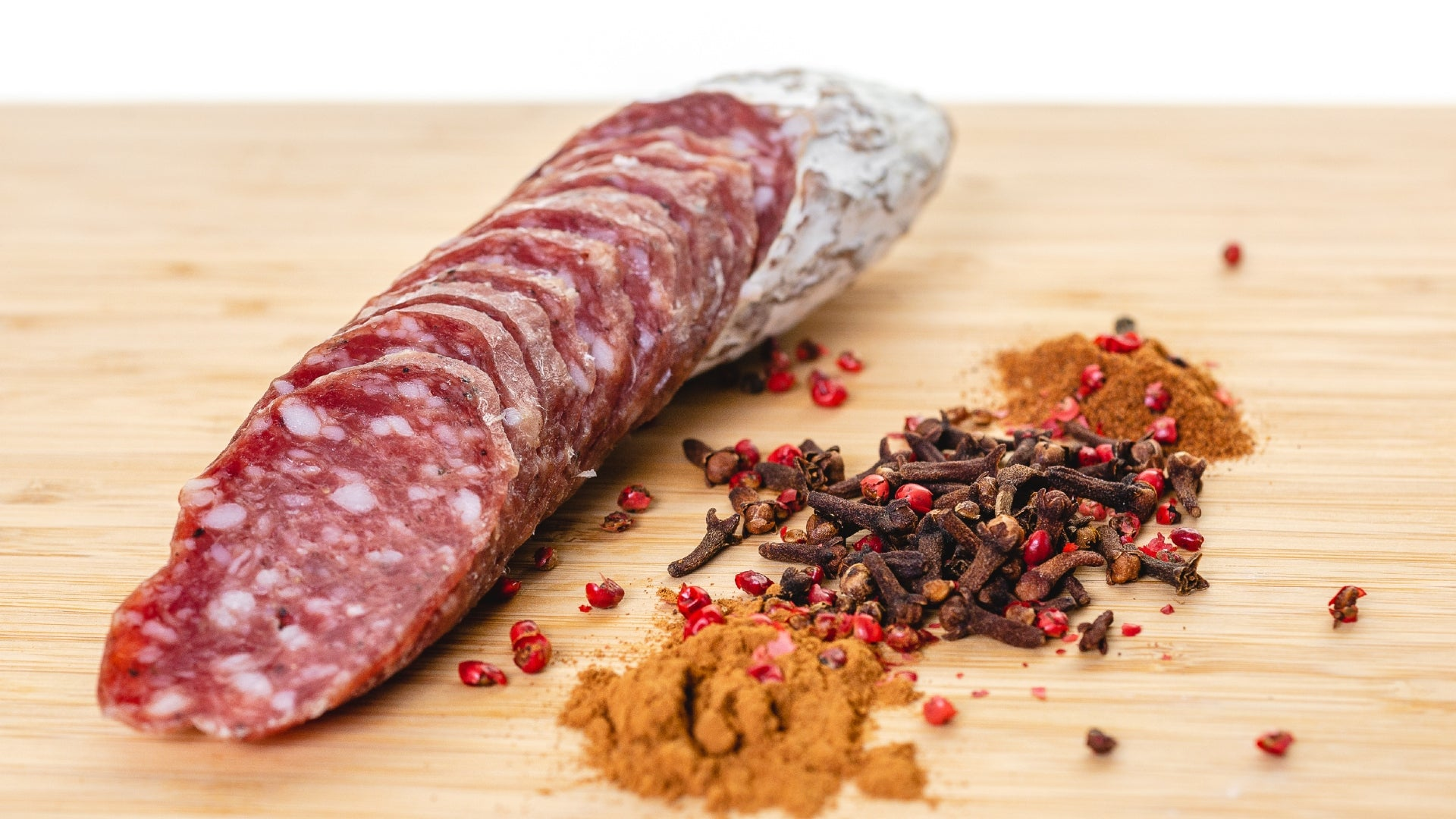 A close up of Rosette De Lyon salami cut into slices on a cutting board next to herbs and spices.