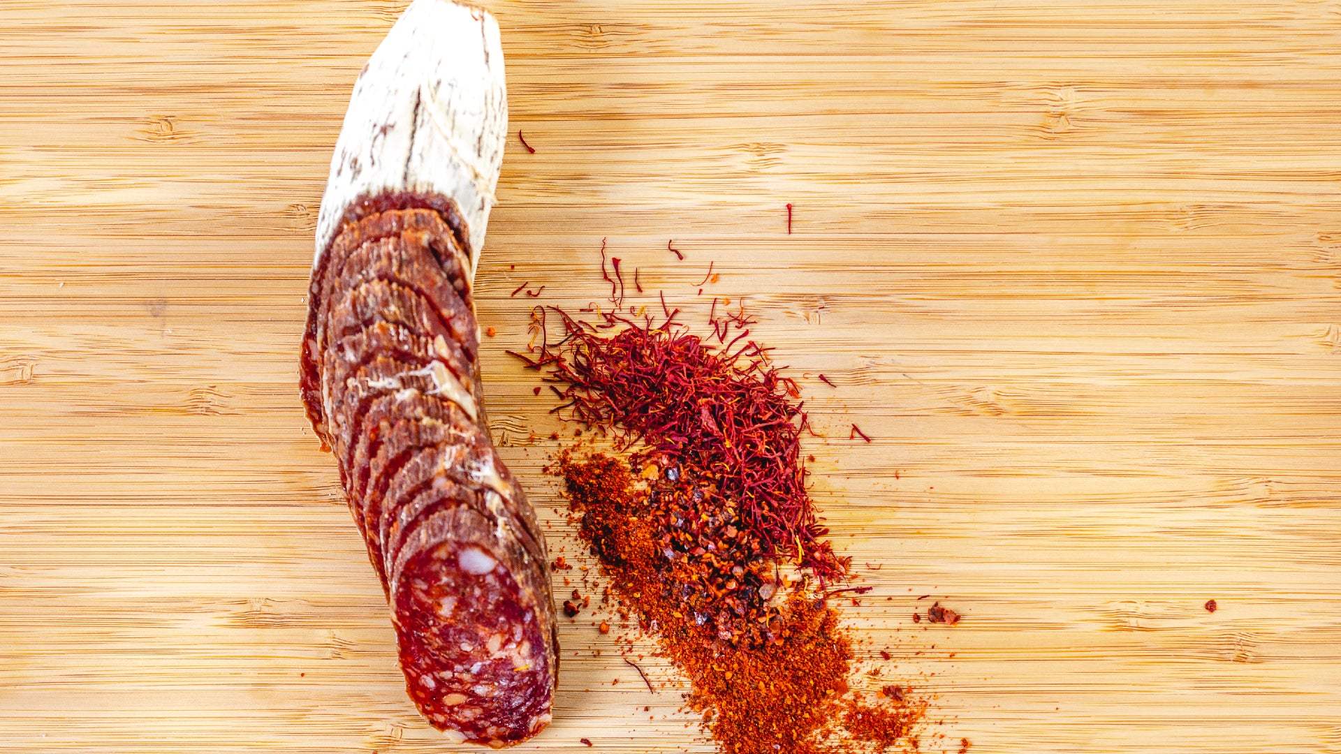 A picture shot from above of Saucisson Basque salami cut into slices on a cutting board next to herbs and spices.