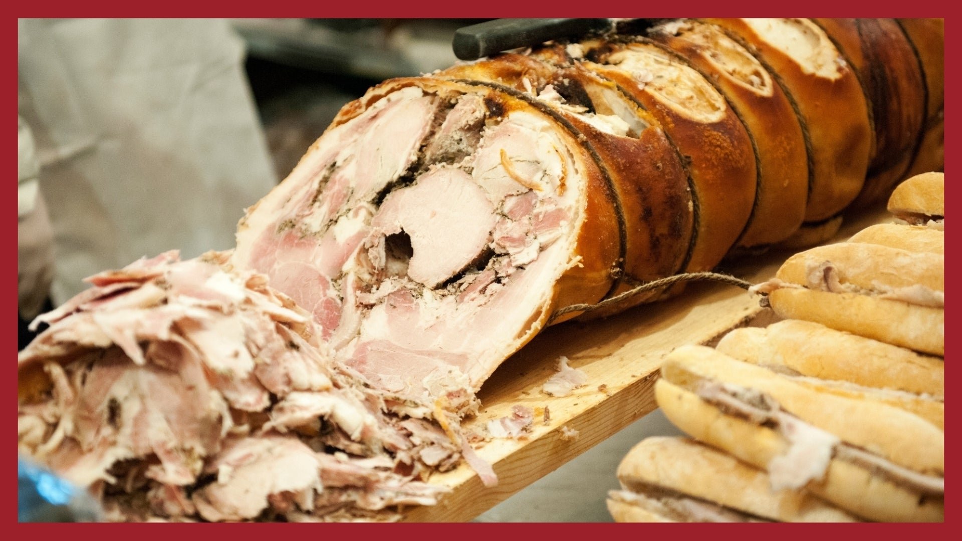 A whole porchetta being cut up into thin slices with porchetta sandwiches in the foreground.