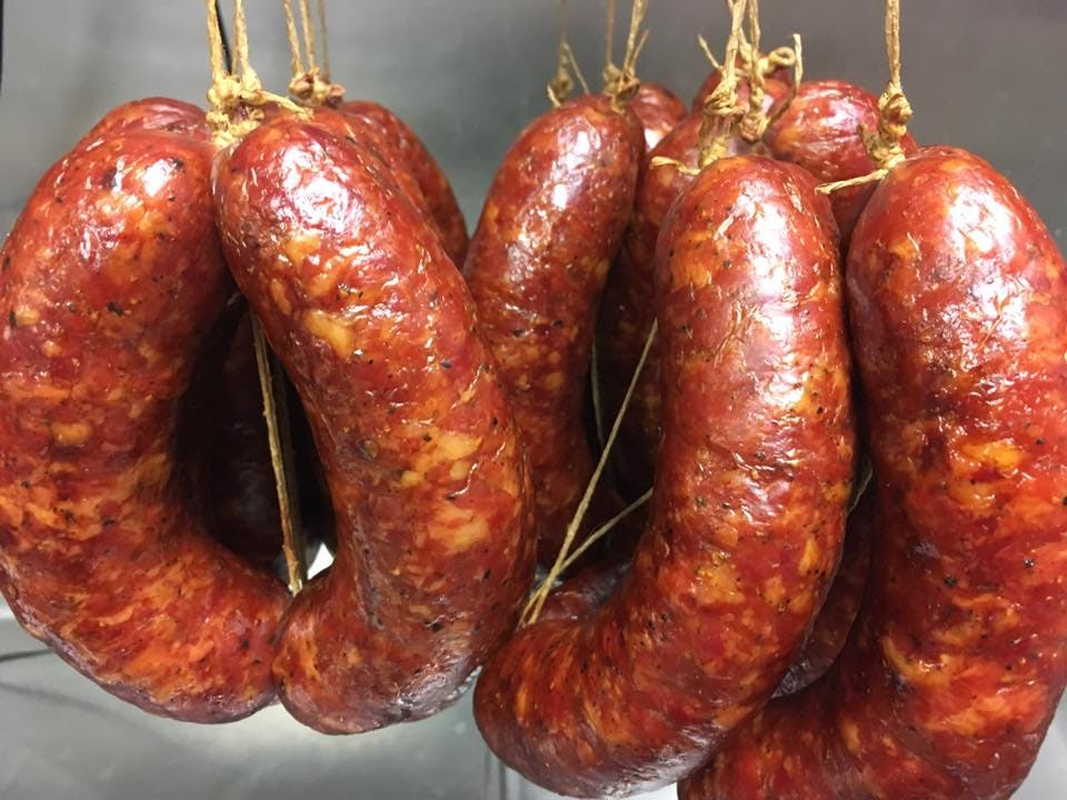 Several smoked kielbasa sausages hanging after being smoked and pictured close up.