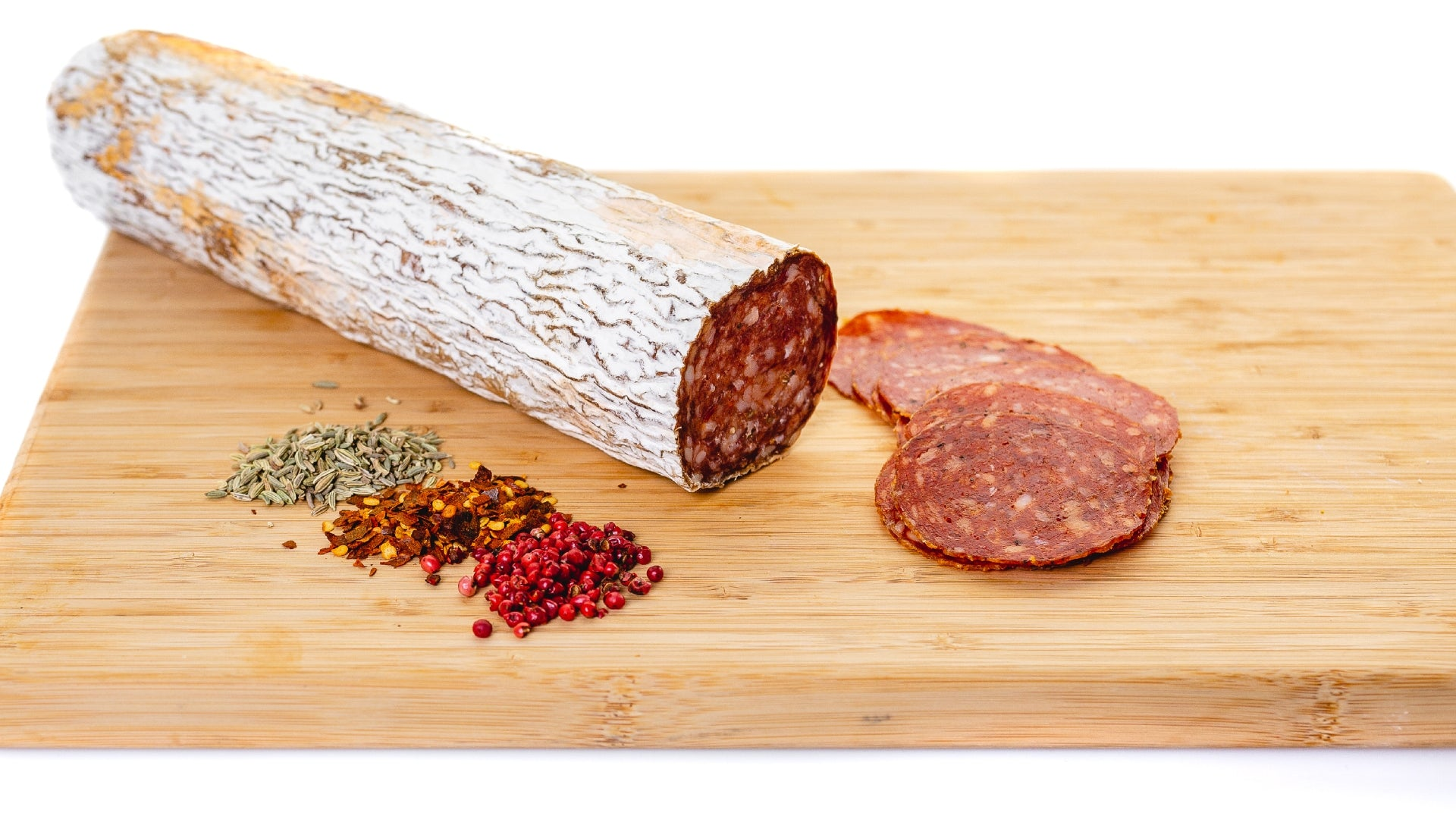 il porcellino salumi's soppressata on a cutting board with slices to the right and spices in the foreground.