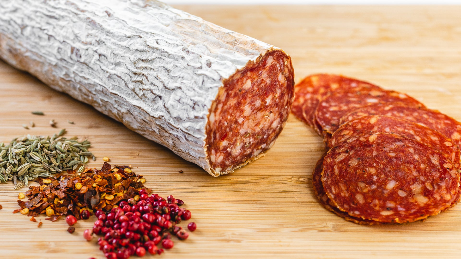 A large chub of Soppressata salami on a cutting board next to herbs and spices and with salami slices in the foreground.