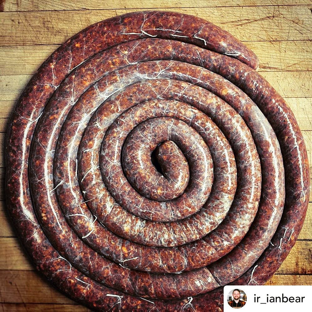 Several feet of specialty sausage rolled up on a butcher table and pictured from above.