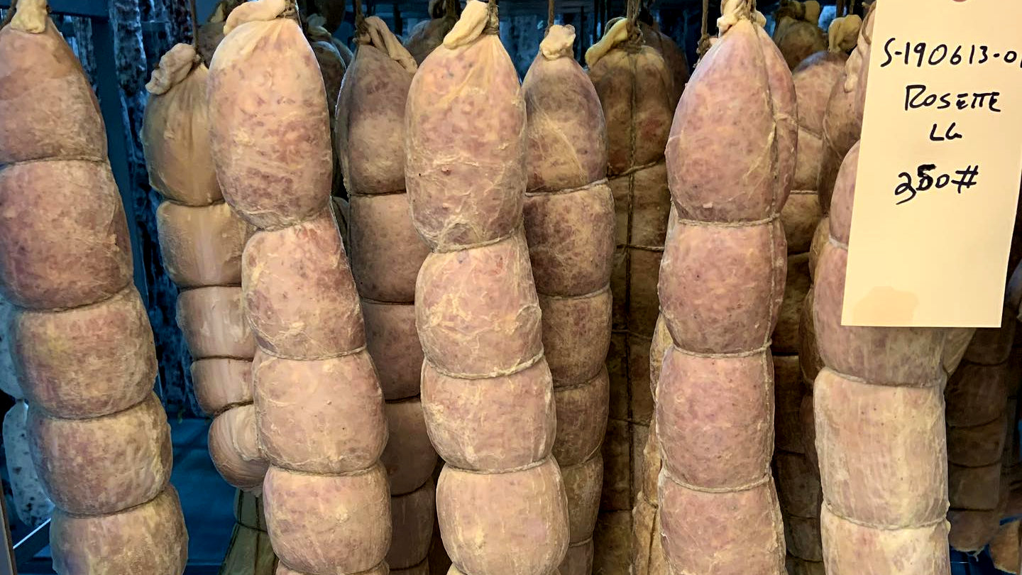 Freshly stuffed salami casings hanging in il porcellino's fermentation room.