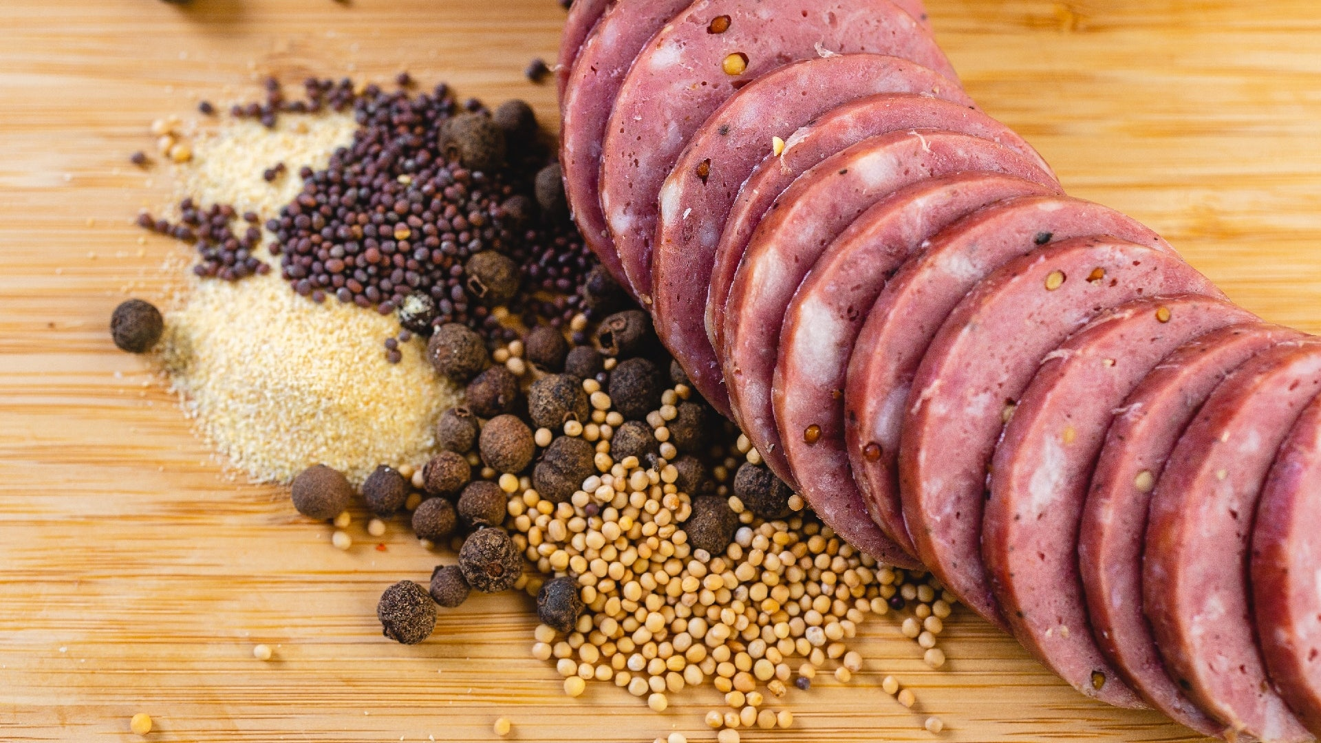A close up picture of slices of summer sausage on a cutting board with herbs and spices next to them.