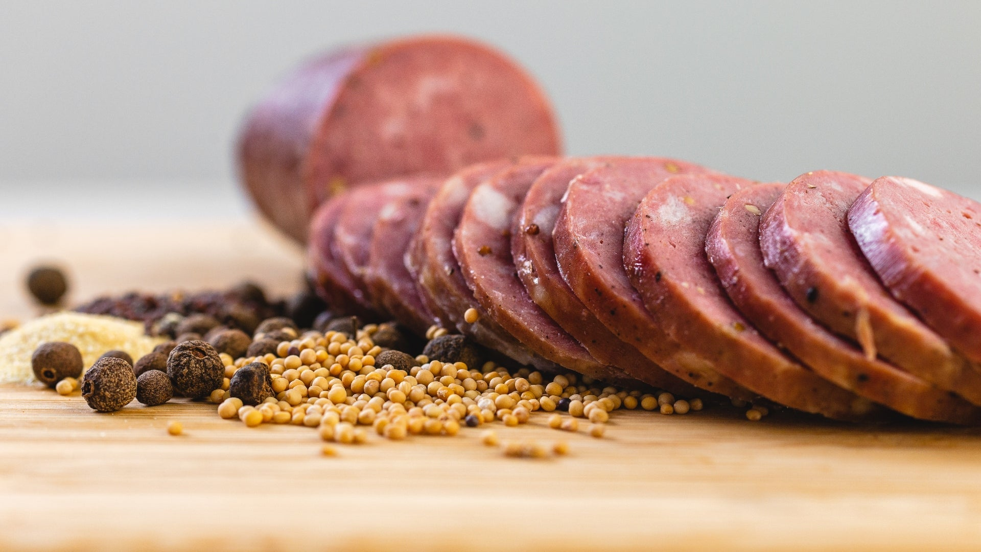 A close up of smoke summer sausage slices on a cutting board next to herbs and spices and with a whole chub of summer sausage in the background.