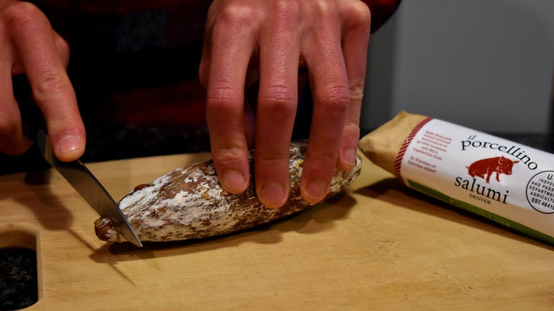 A picture of someone cutting a salami on a cutting board to show that it's okay to touch the protective salami mold.