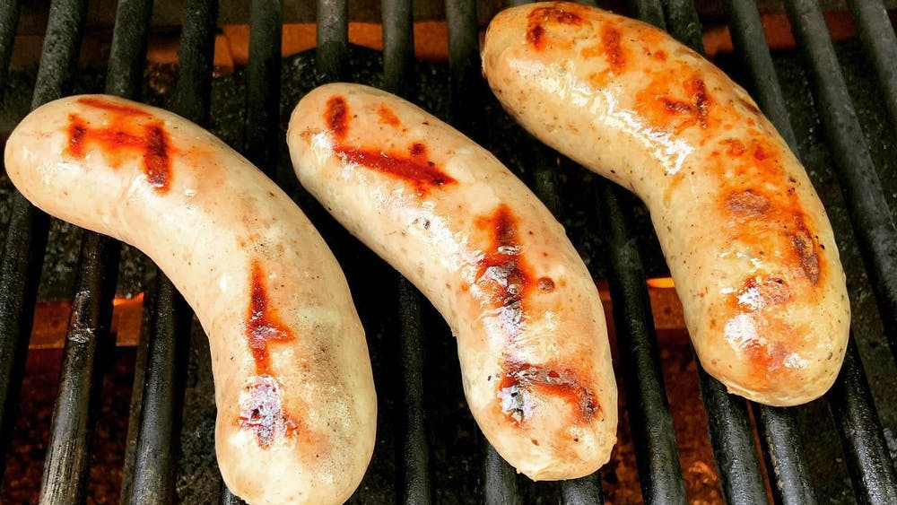 Three sausages being grilled.