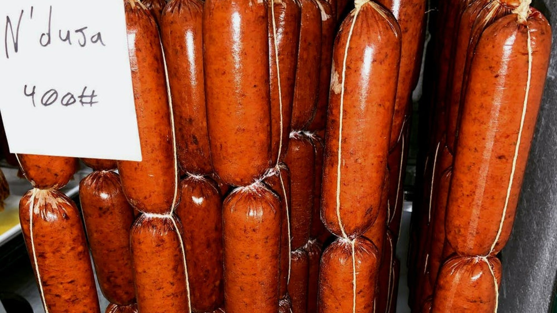 A close up of 'Nduja chubs hanging in the fermentation room.