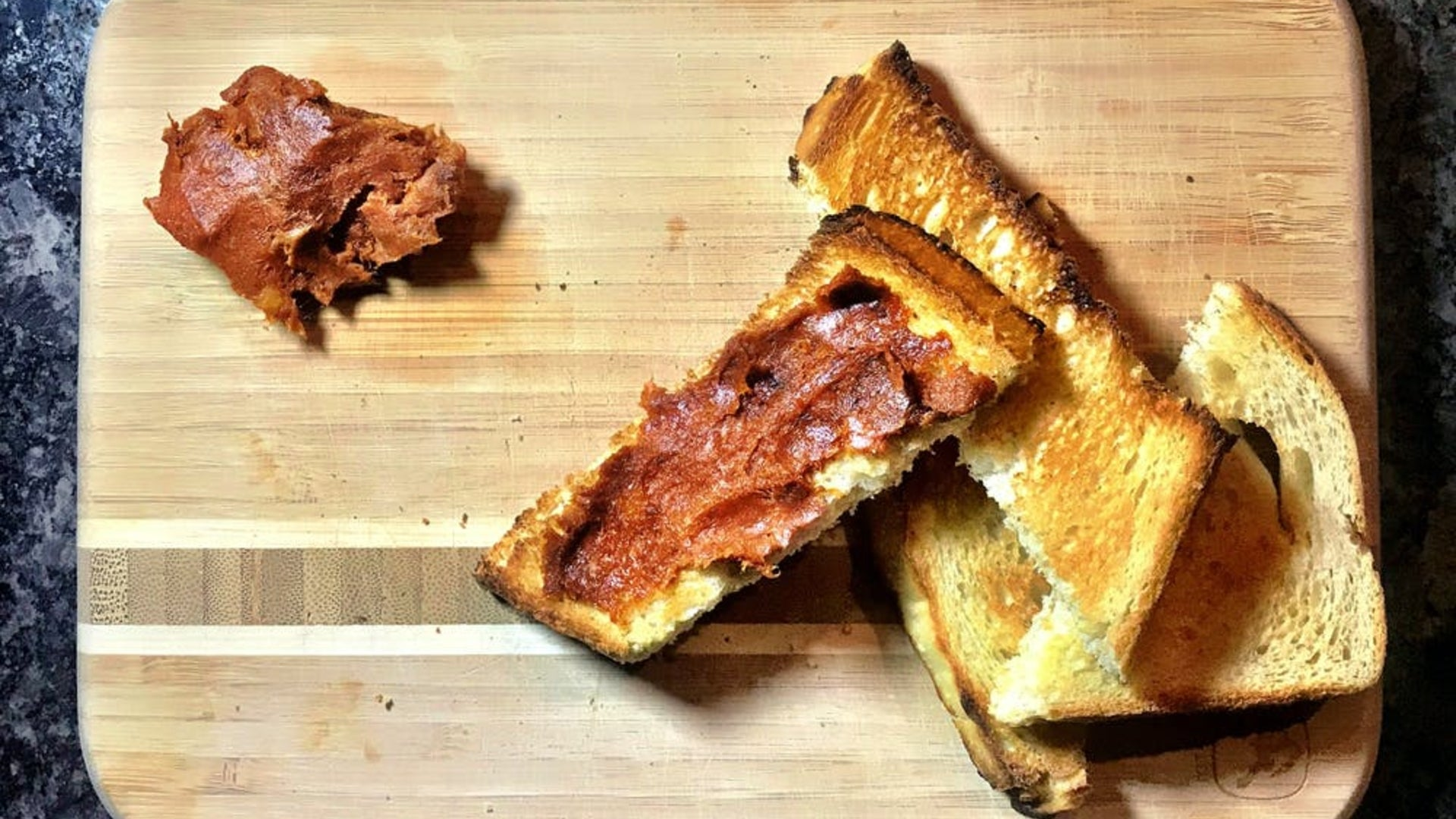 four pieces of crispy toasted bread on a cutting board with 'nduja spread on one piece.