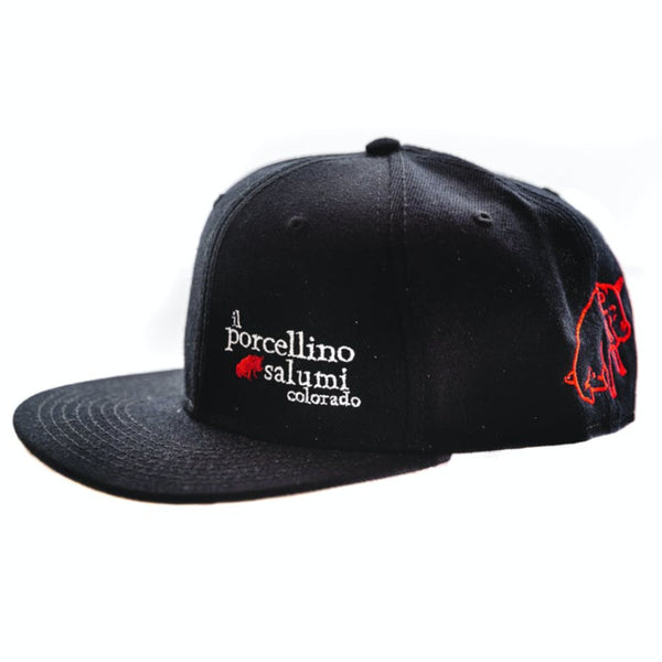 A black baseball hat pictured at the side with il porcellino salumi's name on the front left and the brands logo on the back left of the hat.