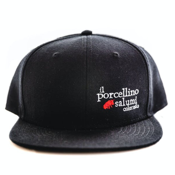 A black baseball hat positioned with the brim facing the camera. Il porcellino salumi's logo is on the front left of the hat.