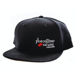 A black baseball hat with il porcellino salumi's logo on it facing the camera at a slight angle.