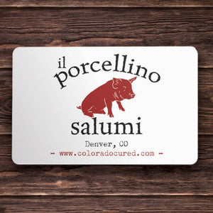 "A picture of a gift card with the words ""il porcellino salumi, Denver, CO"" on it with a wood grain background."