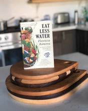Load image into Gallery viewer, Large and small cutting boards stacked with a copy of EAT LESS WATER book displayed on top.