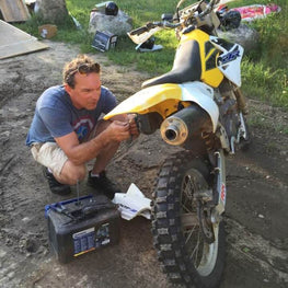 OmegaStrap founder Brad Willodson attending to a repair on a dirt bike.