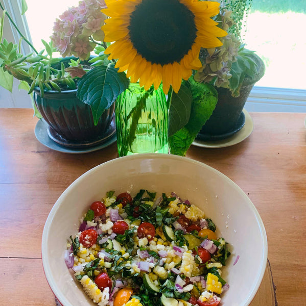 corn and zucchini salad in a bowl with a sunflower