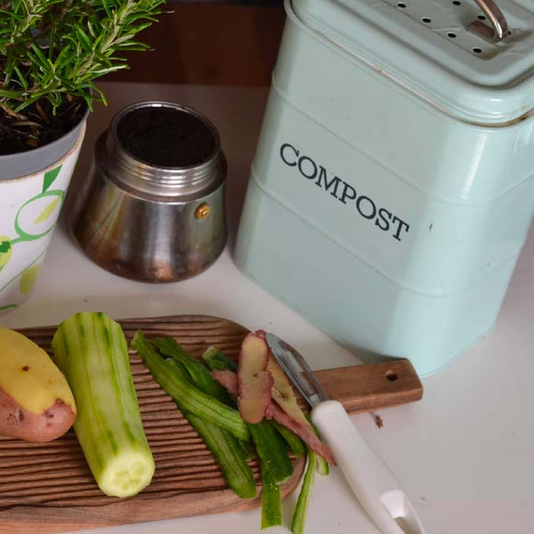 compost bin with produce on a cutting board