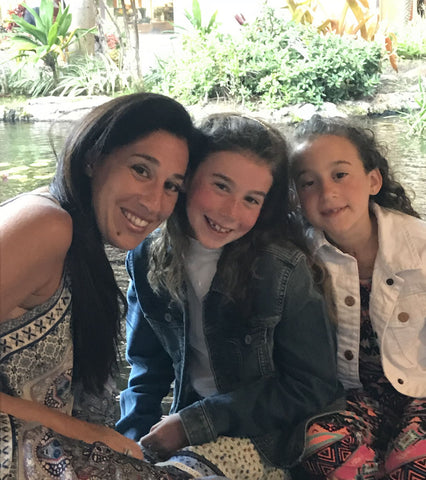 mom with her two daughters sitting together closely in front of pond with foliage behind them