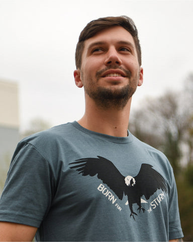 "Model wears a blue/grey short-sleeve shirt with ""Born For The Storm"" text and the image of a flying Eagle."