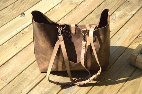 Wanderer shoulder bag with handles fully extended into shoulder straps. Chestnut brown pull-up distressed leather in the sun.