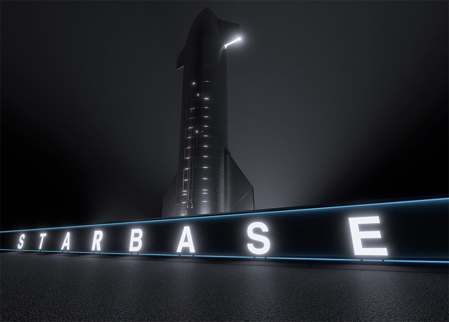 Starship looms in the darkness behind the illuminated Starbase sign at the SpaceX build site in South Texas.
