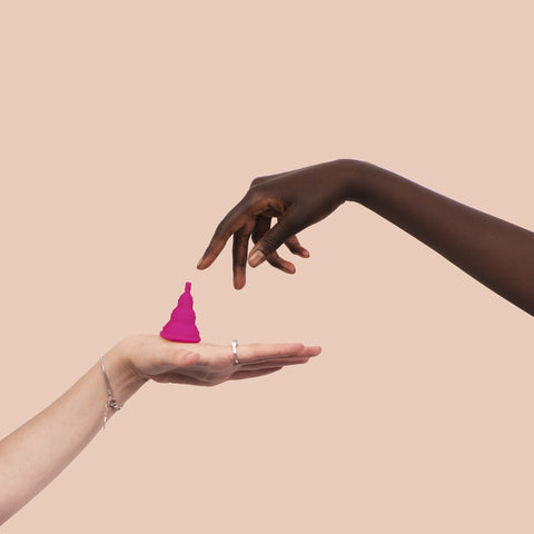 one woman handing another a menstrual cup
