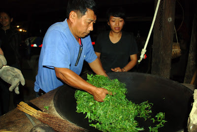 Mr. Gao frying leaves with his bare hands