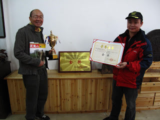 Mr. Yu (on the right) showing off his gold medal trophies