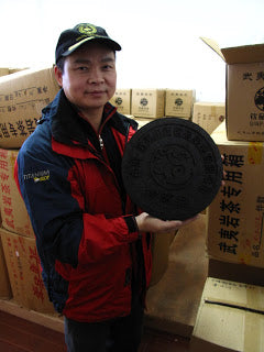 Mr. Yu with a disc of compressed black tea