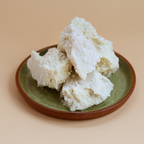 raw pure shea butter in it's natural form displayed on a plate
