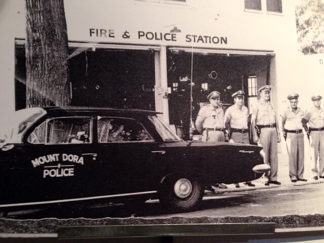 """The building that is now home to Barrel of Books and Games in Mount Dora used to serve as the city's police and fire station. Five officers stand in front of the building next to a car with """"Mount Dora Police"""" on the driver-side door."""