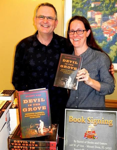 """Crissy Stile, owner of Barrel of Books and Games, stands next to Gilbert King, author of """"Devil in the Grove"""" at a book signing hosted by the store."""