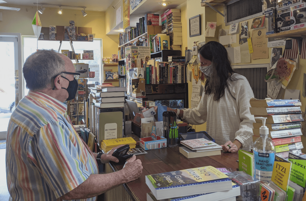 Barrel of Books and Games owner Crissy Stile accepts trade in books from a customer at the checkout counter.