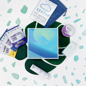 August Turn The Tides AllayBox designed by Wenqing Liu. surrounded by CBD products and shattered glass on plant leaf and white background. Soothe CBD Gummies, MedTerra CBD gummies, TONIC Vibes CBD Chill Tincture, PLUS CBD products, Kiskanu Face Oil. CBD subscription box.