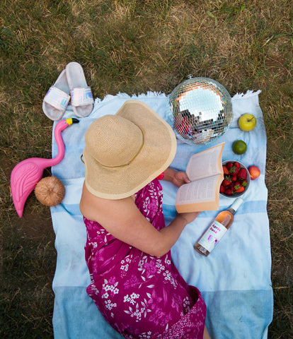 woman drinking with floppy hat summer reading
