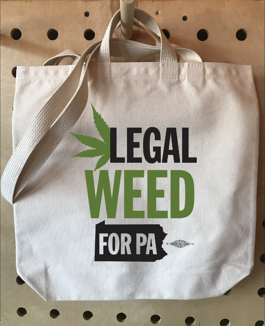 item displays a natural tote bag with the design spelling legal weed black and green ink
