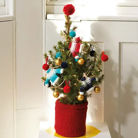 A tiny Christmas tree decorated with knitted jumpers