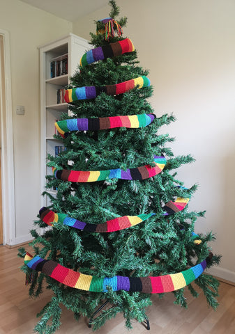 A Christmas tree festooned with a Philadelphia Rainbow in black, brown, red, orange, yellow, green, blue and purple.