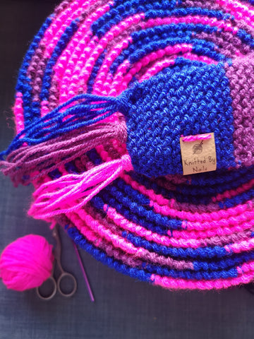 A bi pride tree scarf, in blue, purple and pink, rolled up ready for shipping or storage. The image shows my 'Knitted by Nails' label detail.