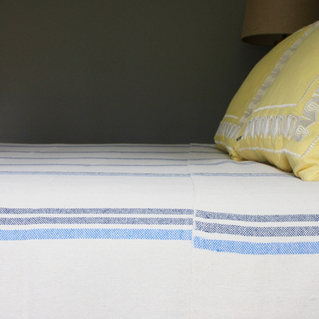 ILDER Handwoven 100% cotton queen blanket in blue stripes by Living Threads Co. artisans in Nicaragua.