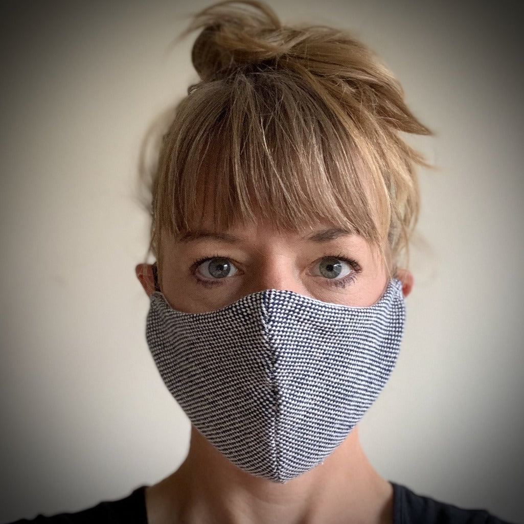 Living Threads Co. reusable face mask in a neutral black and white. Made in collaboration with partner artisans in Nicaragua.