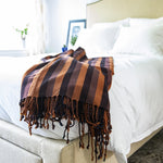 Living Threads Co. handcrafted artisanal natural dye backstrap loom woven blanket in shades of orange, purple and brown.