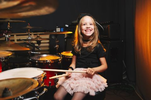 Girl smiling with a drumset
