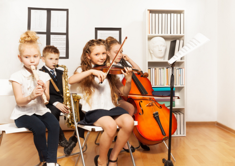 Four children playing a variety of instruments