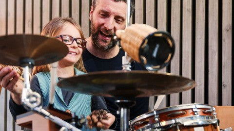 father and daughter having fun playing the drums.