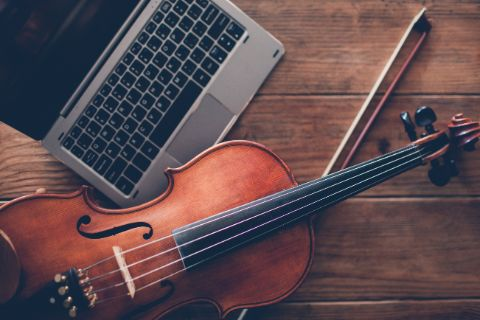 Violin and bow on wood table next to laptop
