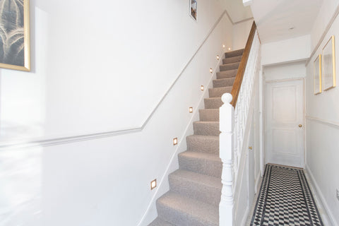 White wall hallway, with machine-made carpet on the stairs, black and white tiles downstairs