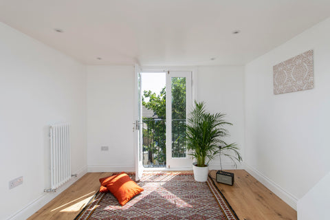 A room with white walls, balcony, handmade carpet with colourful cushions on the floor and a green plant
