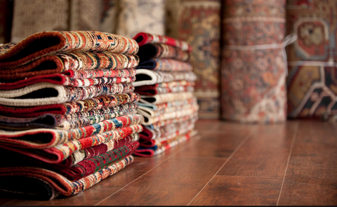 handmade carpets put in a pile with lots of colours